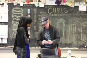 a student in a black head covering speaks to a teacher in a baseball cap in front of a chalkboard.